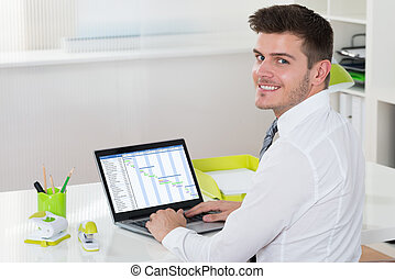 Businessman Working With Gantt Chart On Laptop - Young Happy...