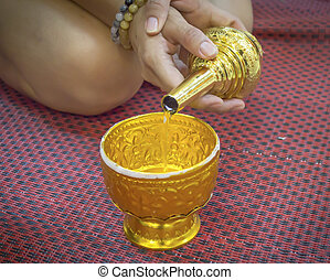 Buddhists grail pouring water sit on mat