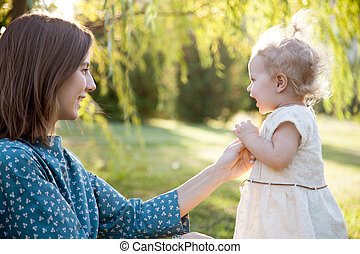Mom playing with tot daughter - Happy young mom and adorable...