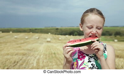 Girl in a field eating watermelon.