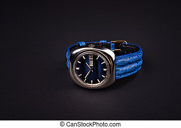 Old men's classic watch with blue strap on black background