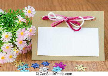 Blank greeting card with pink ribbon and flower on wooden...