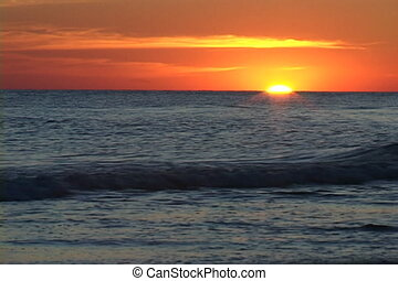 Sun Set On Horizon - Sun sets on the horizon with waves...