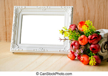 Flowers vase and vintage white picture frame on wooden...