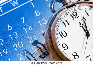 Pocket watch and blue calendar.