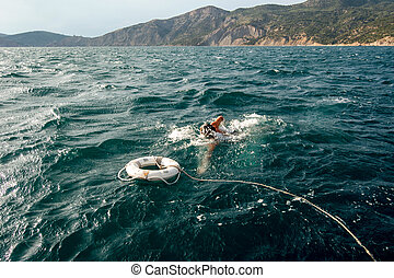 The drowner and the lifebuoy - The drowner is swiming to the...