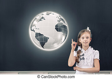 At geography lesson - Cute school girl pointing at globe...