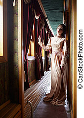 Young woman in beige vintage dress of early 20th century...