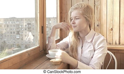 a young, beautiful woman drinking tea