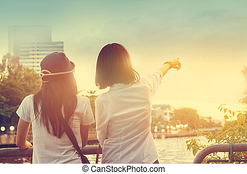 Two women take a sight seeing near the river in the nature sky background, Vintage color tone