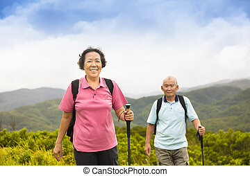 happy senior couple hiking on the mountain