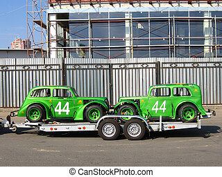 Two racing cars - Two green racing cars at the trailer