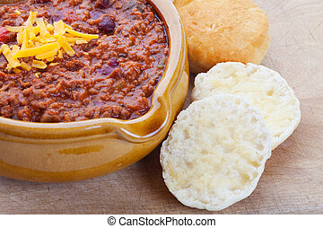 Chili Con Carne topped with shredded cheddar cheese, and...