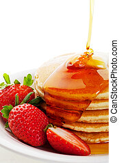 Syrup Pouring on Pancakes - Golden syrup drizzling down over...