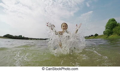 Young girl splashing the water in the lake.
