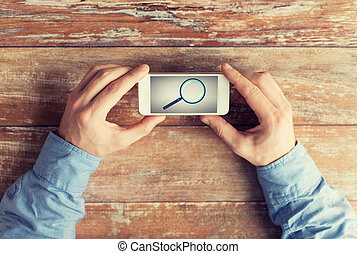 close up of hands with magnifier on smartphone - business,...