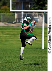 American Football Player - A football player leaping off the...