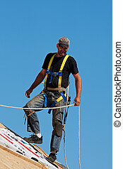 Roofer at Work - Roofer with safety harness shingling a roof...