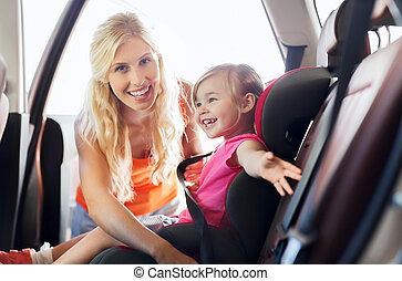 happy mother fastening child with car seat belt - family,...
