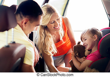 happy parents with little girl in baby car seat - family,...