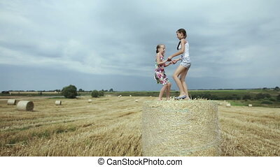 Two girls jump on haystack.