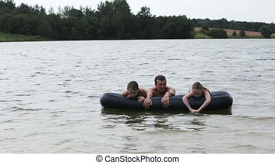 Happy family has a rest on the lake in the summer.