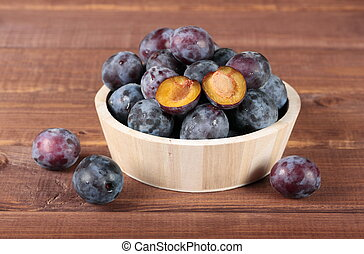 plums in wooden round bowl - Fresh juicy plums in wooden...