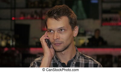 Unshaven young man talking on phone in cafe