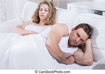Couple arguing in bed - Image of young couple arguing in bed