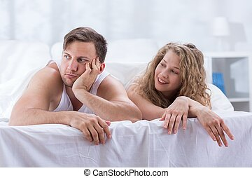Worried man and smiling woman in bed