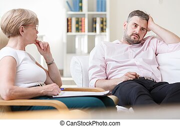 Troubled man talking with psychologist