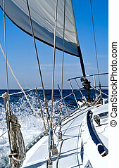 Under sail - A sailboat with reefed jib is hard on the wind,...