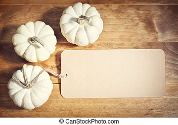 White pumpkins with message card on wooden table