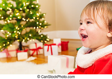 Little girl smiling in front of the Christmas tree