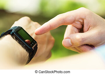 Man looking at his smartwatch - Mans hand pointing at his...