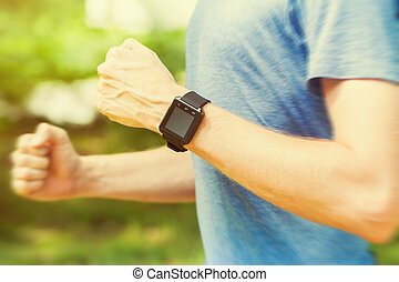 Male runner jogging outside with his smart watch in the...