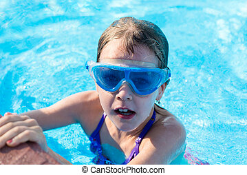 happy girl in blue goggles swimming in the swimming pool