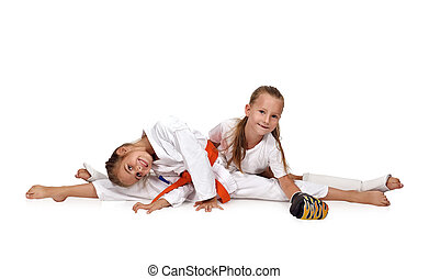 two karate girl sitting on the splits