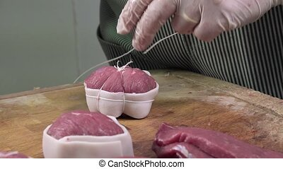 a butcher manufactures veal roulade - The sausage meat is...