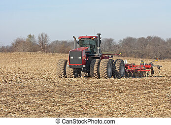 Tractor and Disc - Red farm tractor discing a farm field