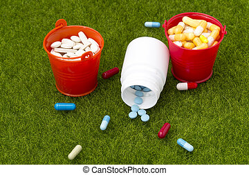 Pills,white bottle of pills and two buckets filled with...