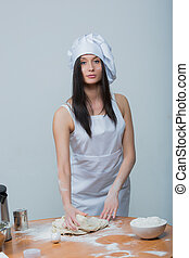 sexy woman in chef uniform knead the dough
