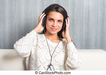 young woman listening music  with headphones in room at home on the sofa look at camera