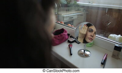 Beautiful woman doing make up looking to the mirror