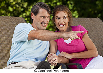 Happy Middle Aged Man Woman Couple Holding Hands and Pointing