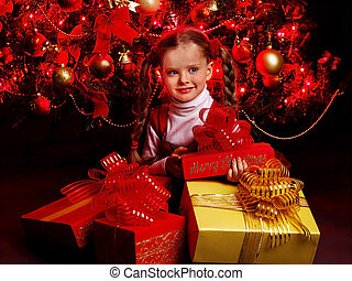 Girl in red dress with gift box near Christmas tree. - Girl...