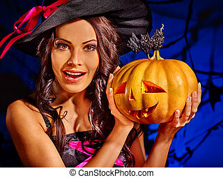 Witch holding pumpkin - Happy witch holding pumpkin on dark...