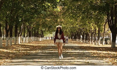 girl walks in autumn alley, girl smiling at the camera