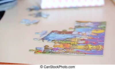 Hands Of Little Child Doing A Puzzle At Table