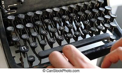 Man printing text with typewriter
